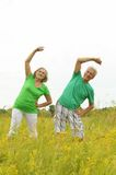 Senior couple doing exercises in the field Stock Photography