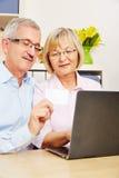 Senior couple doing online shopping with laptop Stock Image