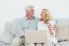 Senior couple doing online shopping on sofa Stock Photos