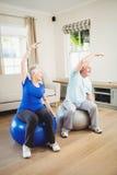 Senior couple doing stretching exercise on exercise ball Royalty Free Stock Image