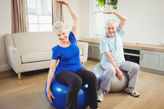 Senior couple doing stretching exercise on exercise ball. At home Stock Photography