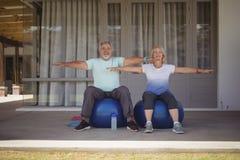 Senior couple doing stretching exercise on exercise ball Royalty Free Stock Photos