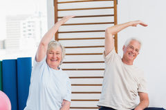 Senior couple doing stretching exercise in fitness studio Royalty Free Stock Photo