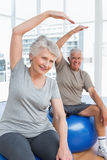 Senior couple doing stretching exercises on fitness balls Stock Photo