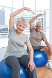 Senior couple doing stretching exercises on fitness balls Stock Photography