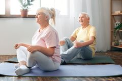 Senior couple doing yoga together at home health care butterfly pose stretching Royalty Free Stock Images
