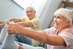 Senior couple doing yoga together at home health care legs stretching close-up Stock Image