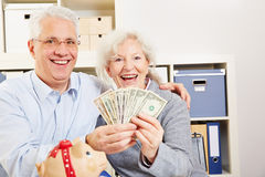 Senior couple with dollar and piggy Royalty Free Stock Photos