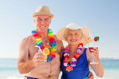 Senior couple drinking a cocktail on the beach Stock Photo
