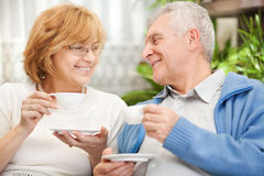 Senior couple drinking coffee. Happy senior couple drinking coffee at home Stock Image