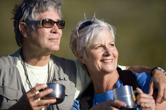 Senior couple drinking coffee from travel cups outdoors royalty free stock photo