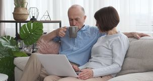Senior couple drinking coffee and using laptop on sofa stock video footage
