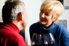 Senior couple drinking red wine. Senior couple having fun clinking glasses with red wine in a romantic setting in front of a fireplace Royalty Free Stock Photography