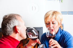 Senior couple drinking red wine. Senior couple having fun clinking glasses with red wine in a romantic setting in front of a fireplace Royalty Free Stock Photos