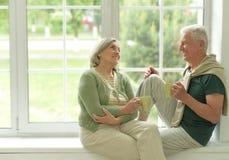 Senior couple drinking tea at home. Happy Senior couple drinking tea sitting on windowsill at home Royalty Free Stock Photos