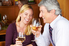 Senior couple drinking wine. Happy senior couple drinking white wine in a restaurant Stock Images
