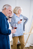 Senior couple drinking wine in art workshop. Side view of senior couple drinking wine in art workshop Royalty Free Stock Photography