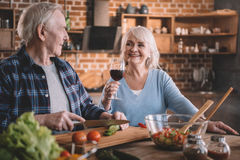Senior couple drinking wine and cooking together Stock Photos