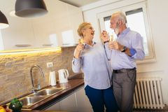 Couple drinking wine in home kitchen royalty free stock images