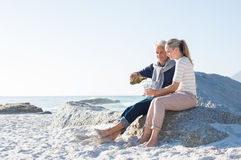 Senior couple drinking wine. Senior men pouring white wine in glasses for celebrating anniversary with his wife. Happy mature couple sitting on beach while men Stock Photography