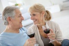 Senior couple drinking wine and talking on sofa Royalty Free Stock Image