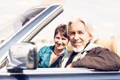 Senior Couple Driving A Convertible Classic Car Stock Photo