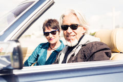 Senior Couple Driving A Convertible Classic Car Stock Images