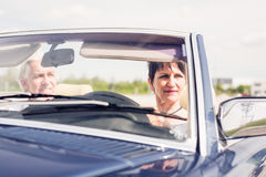 Senior Couple Driving A Convertible Classic Car Stock Photography
