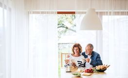 Senior couple eating breakfast at home. An old men and women sitting at the table, relaxing stock photography