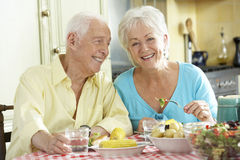 Senior Couple Eating Meal Together In Kitchen Stock Photos