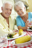 Senior Couple Eating Meal Together In Kitchen Stock Image