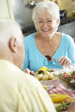 Senior Couple Eating Meal Together In Kitchen Royalty Free Stock Images