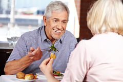 Senior couple eating in restaurant Stock Photos