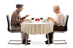 Senior couple eating a salad at a restaurant table stock images
