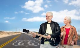Senior couple with electric guitar over route 66 Stock Photo