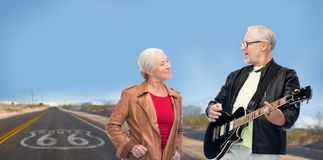 Senior couple with electric guitar over route 66 Stock Image