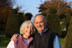 Senior couple embrace in formal gardens. Stock Image