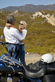 Senior couple embrace next to motorcycle in the desert Royalty Free Stock Images