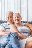 Senior couple embrace sitting on sofa smile Stock Image