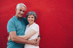 Senior couple embracing against red wall Stock Photos