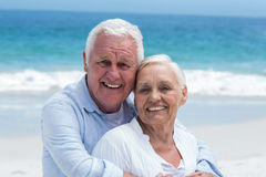 Senior couple embracing with arms around Stock Photos