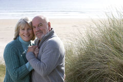 Senior couple embracing on beach, smiling, portrait Stock Images