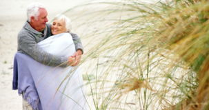 Senior couple embracing each other on the beach stock video footage