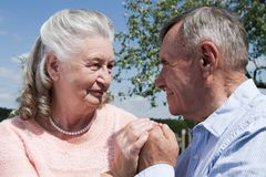Senior couple embracing each other in countryside Stock Photos