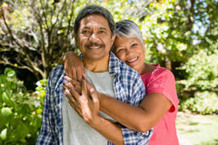 Senior couple embracing each other in garden on a sunny day Stock Photo