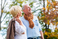 Senior couple embracing each other lovingly. Senior couple, husband and wife, embracing each other lovingly in autumn park Stock Photo