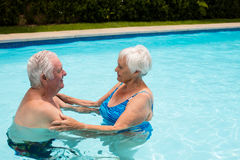 Senior couple embracing each other in the pool Stock Photos