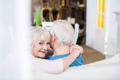 Senior couple embracing at home, woman looking at camera Royalty Free Stock Photo