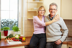 Senior couple embracing in kitchen Stock Photos