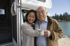 Senior couple embracing outside of RV on lake Stock Images